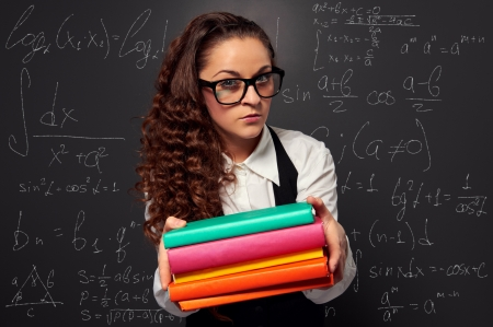 young teacher in glasses offering books over chalkboard photo