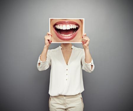 dentista: mujer sosteniendo la foto con una gran sonrisa. Foto de concepto sobre fondo oscuro Foto de archivo