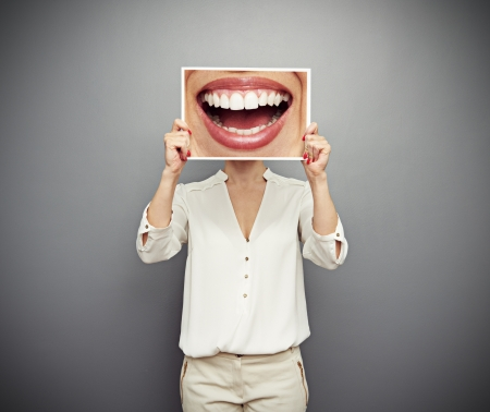 laughter: woman holding picture with big smile. concept photo over dark background