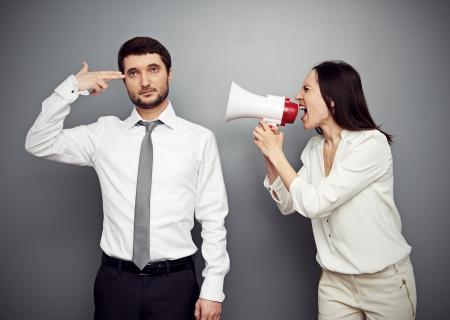jefe enojado: mujer enojada gritando en el hombre cansado sobre fondo oscuro