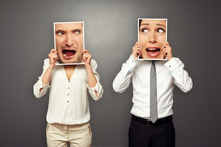 man and woman holding screaming faces. concept photo over grey background Stock Photo