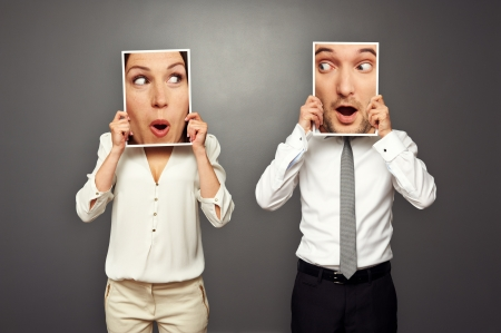 swap: man and woman holding surprised faces. concept photo over grey background