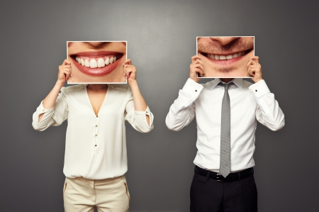 merriment: woman and man holding pictures with big smile. concept photo over dark background Stock Photo