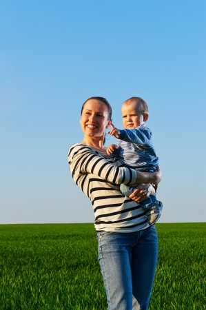 merriment: young mom holding her son and smiling Stock Photo