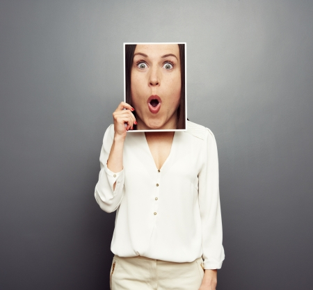 young woman covering image with big amazed face. concept photo over grey background Stock Photo - 19377958
