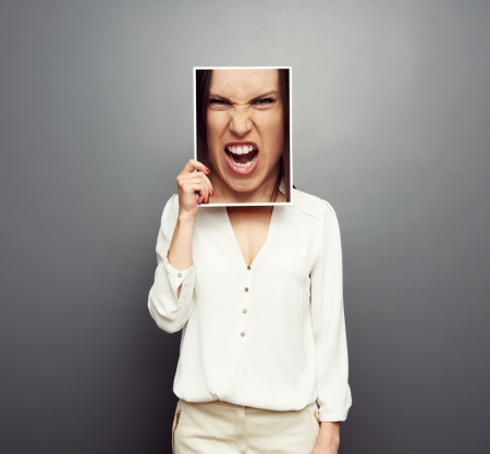 young woman covering image with big angry face. concept photo over grey background Stock Photo - 19377972