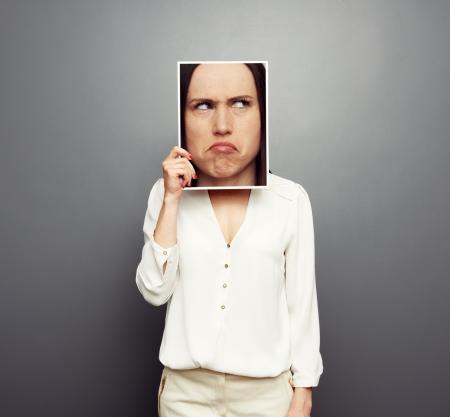 mujer joven que cubre la imagen con la cara pensativa grande. Foto de concepto sobre fondo gris Foto de archivo