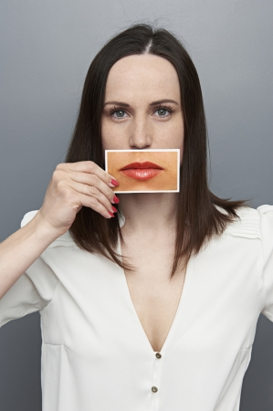 moods: young woman holding picture with big lips and looking at camera Stock Photo