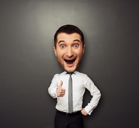 grosse tete: Homme d'affaires heureux avec la grosse t�te montrant thumbs up. dr�le d'image sur fond sombre Banque d'images