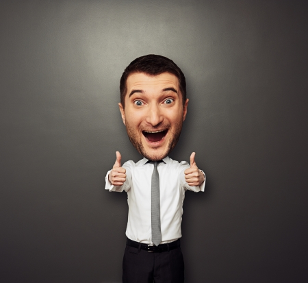 big idea: happy businessman with big head showing two thumbs up and laughing. funny picture over dark background Stock Photo