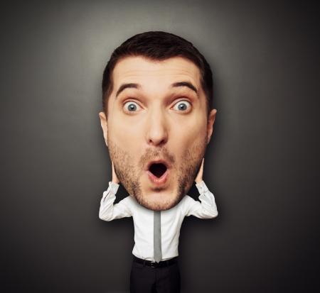 surprised: imagen divertida del hombre sorprendido con la cabeza grande sobre fondo oscuro