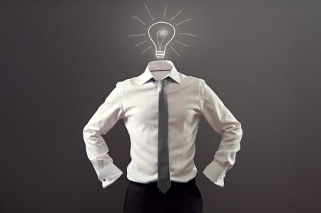 niewidoczny: anonimowy mężczyzna w białej koszuli i czarne spodnie posiadające pomysł na ciemnym tle