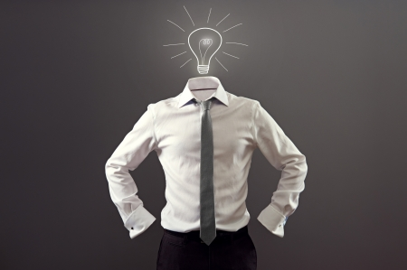 anonymous man in white shirt and black trousers having an idea over dark background photo