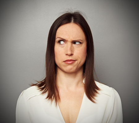 suspiciously: young brunette looking with misunderstand. studio portrait over grey background Stock Photo