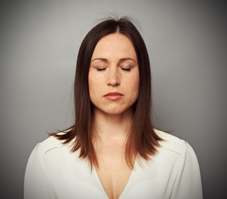 closed eye: calm woman with closed eyes over grey background