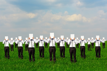 crowd of businessmen with white empty posters. concept photo on green field Stock Photo