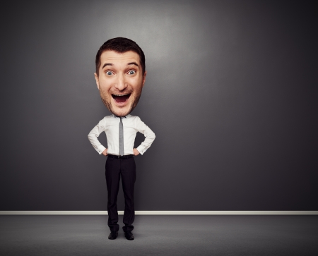 full-length picture of excited businessman with big head over dark background photo