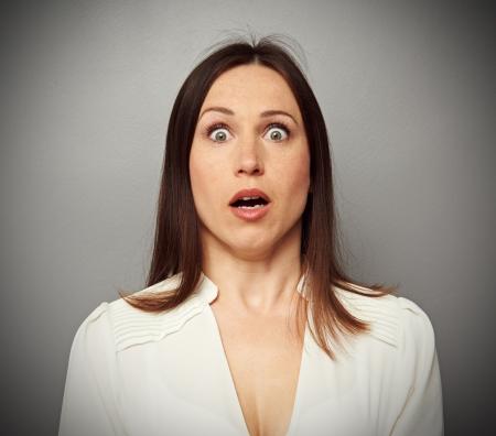 cara sorprendida: asustada mujer mirando a la cámara sobre fondo oscuro