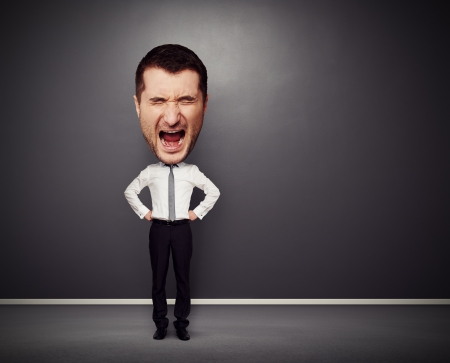 malice: full-length picture of angry businessman with big head over dark background