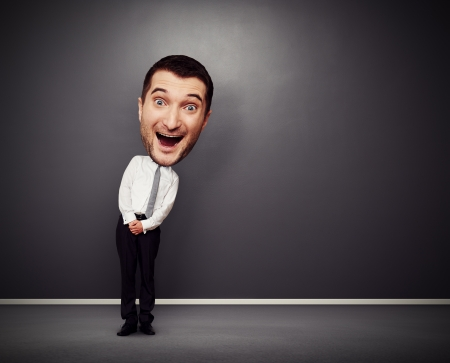 gladness: full-length picture of funny businessman with big head over dark background