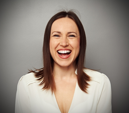merriment: emotional portrait of happy and laughing woman over grey background
