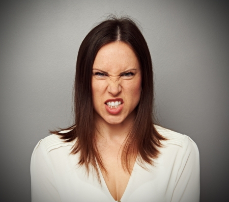 grin: mad woman baring her teeth over grey background Stock Photo