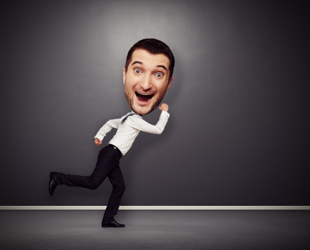 big smile: funny picture of merry running man with big head over dark background Stock Photo