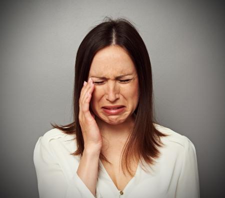 mujer llorando: joven morena está llorando sobre fondo oscuro