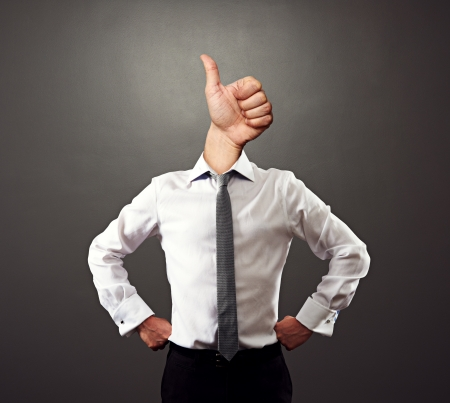 business man with thumbs up gesture instead of the head over grey background photo