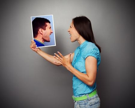 irritate: concept photo of couple in quarrel over dark background