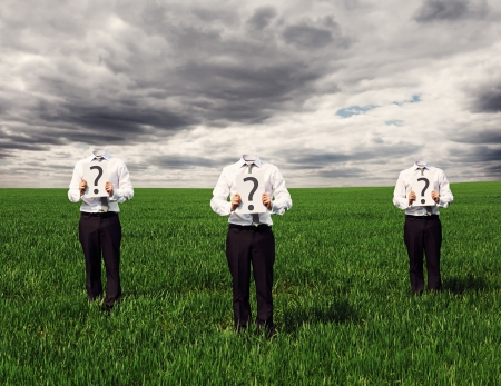 faceless businessmen standing on the green grass and holding placard with question mark photo