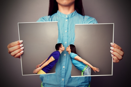 lacerated: woman holding the lacerated photo of young kissing couple