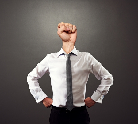 business man with fist instead of the head over grey background photo