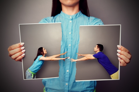 divorce: woman holding the lacerated photo of young couple over grey background Stock Photo