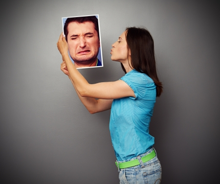 sorrowfully: young woman kissing the photo of depressed man