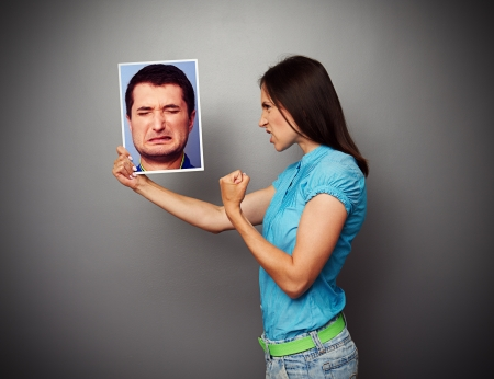 aggressive woman showing threatening fist to man photo