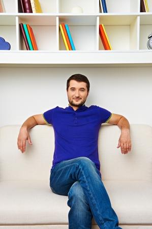 divan: joven sentado en el sof� y sonriendo