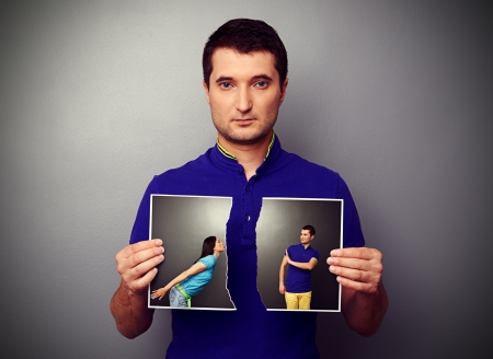 lovers quarrel: serious young man tearing the photo of couple Stock Photo