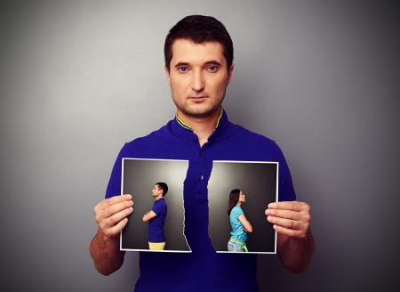 serious young man holding the lacerated photo of young couple in quarrel photo