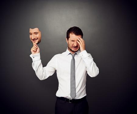 persona deprimida: llorando hombre máscara que sostiene con la cara sonriente