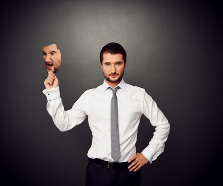 wrathful: serious businessman holding mask with bad mood