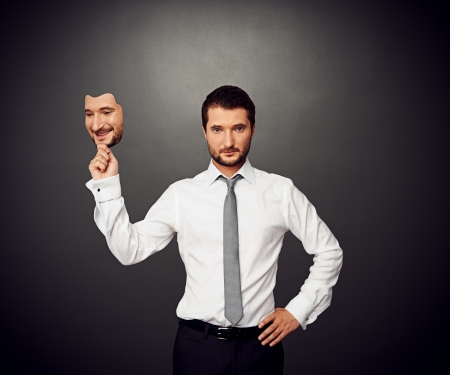 serious businessman holding mask with good mood photo