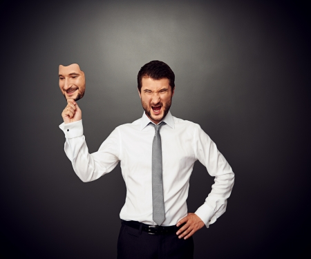 wrathful businessman holding mask with smiley face Stock Photo - 20019902