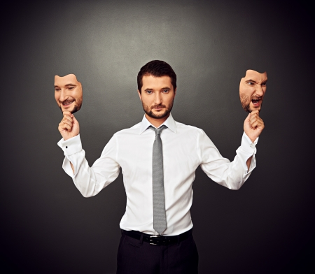 dissimulation: serious businessman holding two masks with different mood Stock Photo