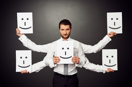 good mood: serious businessman with five hands holding placards with smile Stock Photo