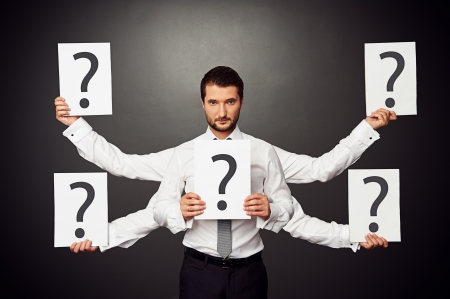 serious businessman with five hands holding placards with question marks photo