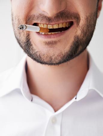 dientes sucios: cerca de la foto del hombre que fuma con los dientes amarillos sucios