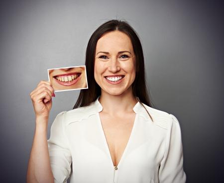 dientes sucios: sonriente mujer sana sosteniendo la foto con los dientes amarillos sucios Foto de archivo