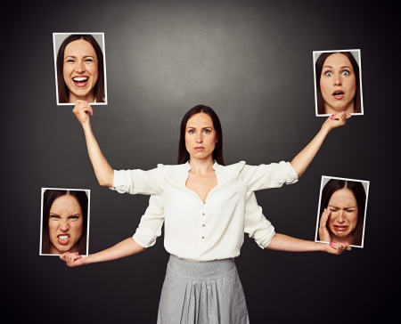 serious young woman holding pictures with different mood