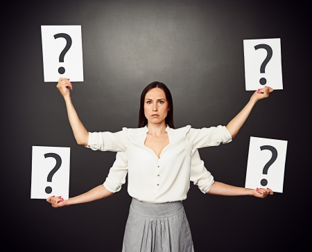 serious woman with four hands holding placards with question mark photo